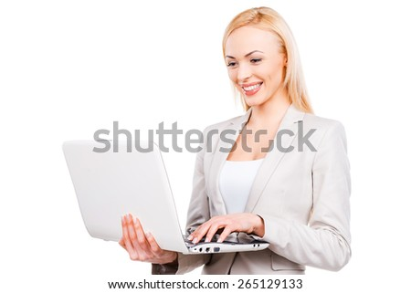 Confident businesswoman at work. Confident mature businesswoman working on laptop and smiling while standing against white background - stock photo