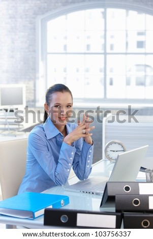 Confident businesswoman at work, sitting at office desk, smiling at camera. - stock photo