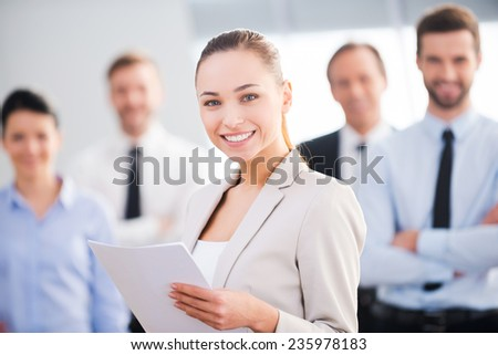 Confident businesswoman. Attractive young businesswoman holding documents and smiling while his colleagues standing in the background  - stock photo