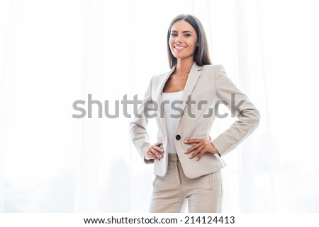 Confident businesswoman. Confident young businesswoman in suit holding hands on hip and smiling - stock photo