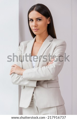 Confident businesswoman. Confident young businesswoman in suit keeping arms crossed and looking at camera  - stock photo