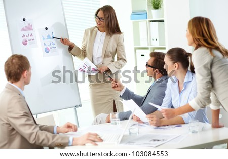 Confident businesswoman explaining her ideas to colleagues at meeting - stock photo