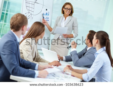 Confident businesswoman explaining something to colleagues at meeting - stock photo