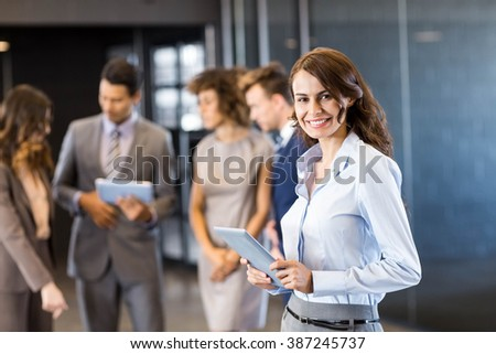 Confident businesswoman in office with her team in the background - stock photo