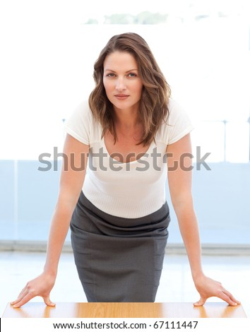 Confident businesswoman posing leaning on a table - stock photo