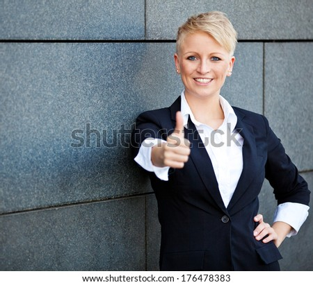 Confident businesswoman showing thumbs up - stock photo