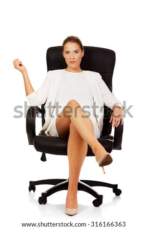 Confident businesswoman sitting on armchair. - stock photo
