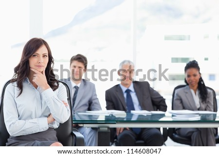 Confident businesswoman sitting with her hand on her chin in front of her serious team - stock photo
