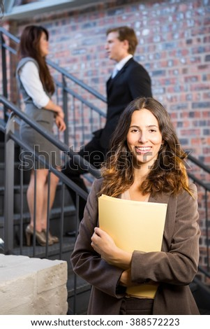 Confident businesswoman standing in office holding document - stock photo