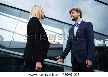 Confident businesswoman talking with his colleague standing near office building, business professionals having a discussion, office people talking about the work standing near skyscraper - stock photo