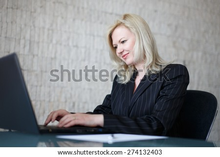 Confident businesswoman typing on laptop in office - stock photo