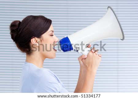 Confident businesswoman yelling through a megaphone at work - stock photo