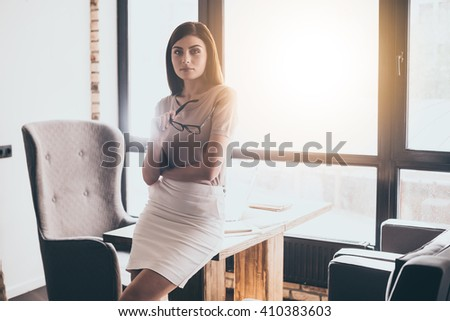 Confident businesswoman. Young beautiful woman looking at camera and carrying glasses in her hand while leaning on table in front of window at her working place - stock photo