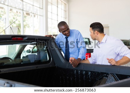 confident car salesman selling a car to middle aged customer - stock photo