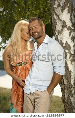 Confident casual caucasian man with pretty blonde girlfriend outdoors. Leaning against tree, smiling. hands in pocket. - stock photo