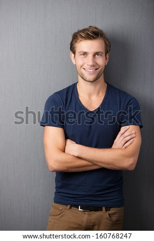 Confident casual unshaven young man standing with his arms folded looking at the camera with a wide friendly smile - stock photo