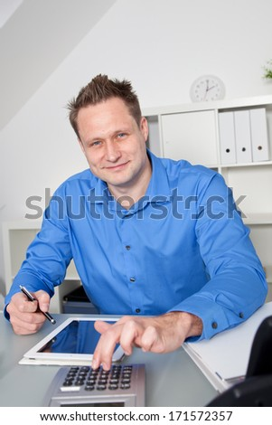 Confident Caucasian business man smiling and wearing a blue shirt while working at his desk with a PC tablet and a desktop calculator - stock photo
