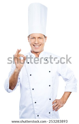 Confident chef. Confident mature chef in white uniform gesturing OK sign and smiling while standing against white background - stock photo
