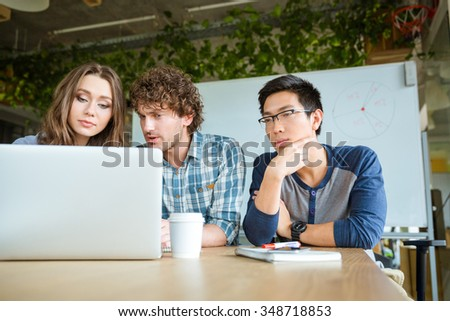 Confident concentrated students learning and studying with laptop in classroom - stock photo