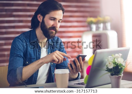 Confident creative businessman using smartphone in office - stock photo