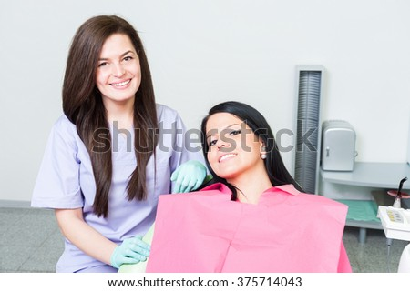 Confident dentist doctor and smiling female patient posing in dental office - stock photo