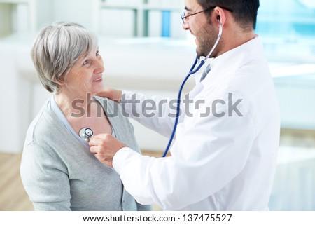Confident doctor examining his senior patient in hospital - stock photo