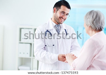 Confident doctor looking at his senior patient while speaking to her - stock photo