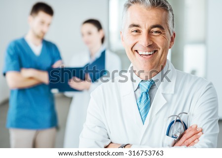 Confident doctor posing and smiling at camera and medical staff checking medical records on background - stock photo