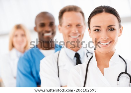 Confident doctors team. Confident female doctor looking at camera and smiling while her colleagues standing in a row behind her - stock photo