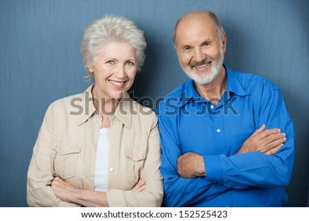 Confident elderly couple with folded arms standing side by side smiling at the camera against a green background - stock photo