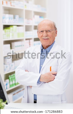 Confident elderly male pharmacist standing in the pharmacy in a white lab coat behind the counter with folded arms smiling at the camera - stock photo