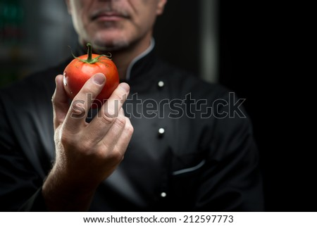 Confident elegant chef holding a delicious tomato on dark background. - stock photo