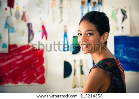 Confident entrepreneur, portrait of happy hispanic young woman working as fashion designer and dressmaker in atelier - stock photo