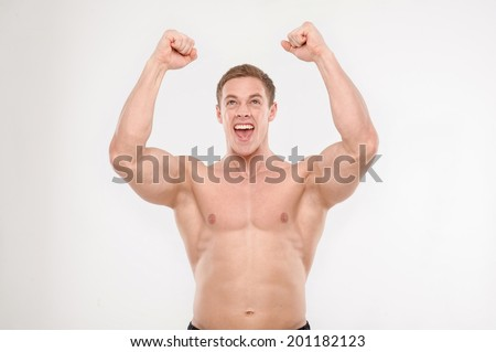 Confident excited athletic man celebrating success raising fist isolated on white. Concept of success, victory, sport result - stock photo