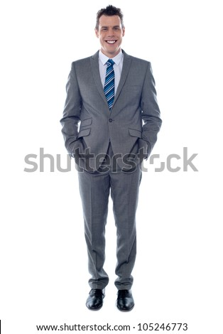 Confident executive posing with hands in pocket. Smiling at camera - stock photo