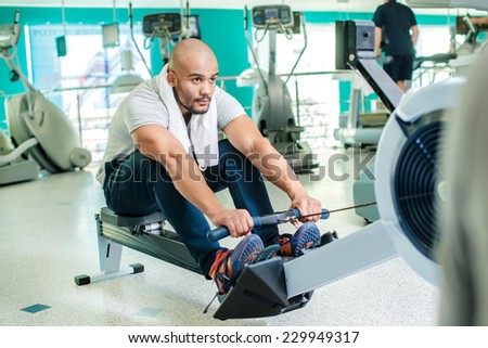 Confident exercise on rowing machine. Young man at the gym on rowing machine in full force. - stock photo