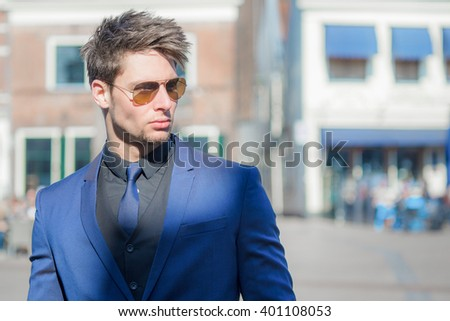 Confident fashionable male model. Sunny and bright street. - stock photo