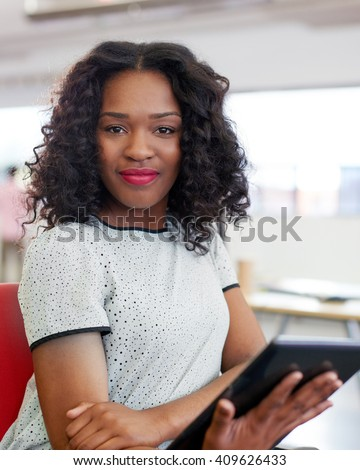 Confident female designer working on a digital tablet in red creative office space - stock photo