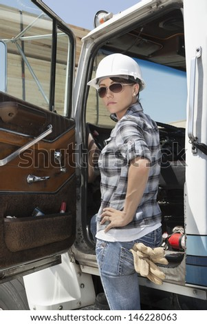 Confident female industrial worker standing by vehicle door with hand on hip - stock photo