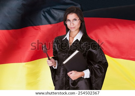 Confident Female Judge With Law Book And Wooden Gavel Standing In Front Of German Flag - stock photo