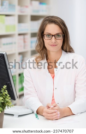 Confident female pharmacist wearing glasses standing behind the counter in the pharmacy looking at the camera - stock photo