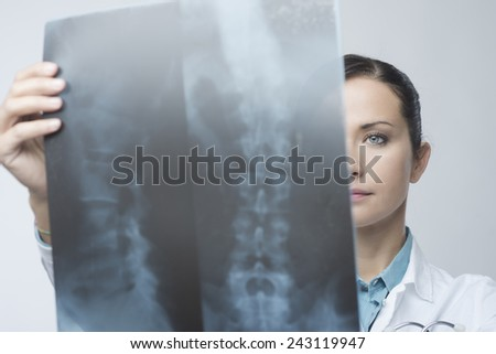 Confident female radiologist checking x-ray image of spinal column. - stock photo
