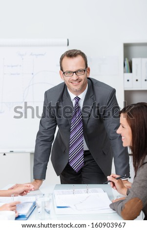 Confident friendly business manager or corporate executive standing leaning on a table at a meeting with colleagues, looking at the camera with a smile - stock photo