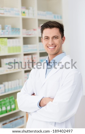Confident friendly male pharmacist standing with folded arms in his white lab coat in the pharmacy with shelves of stock smiling at the camera - stock photo