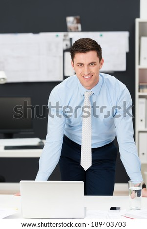 Confident friendly young businessman leaning forwards as he stands at his desk smiling at the camera - stock photo