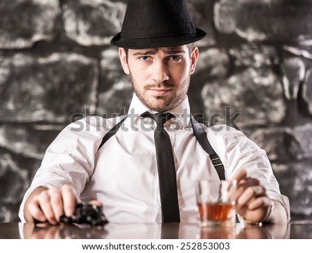 Confident, gangster man in shirt, suspenders and hat is sitting at the table with a glass of whisky and gun. - stock photo