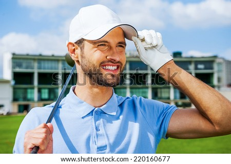 Confident golfer. Low angle view of young happy golfer holding driver and adjusting his cap while standing on golf course - stock photo