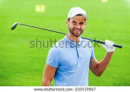 Confident golfer. Young happy golfer carrying driver on shoulder and smiling while standing on golf course - stock photo