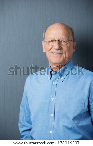 Confident grey-haired balding senior man with a friendly smile standing against a dark grey background with copyspace and slight vignetting - stock photo