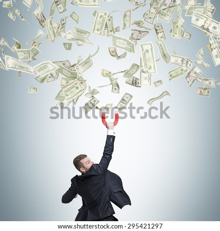 Confident handsome businessman attracts dollar notes using a magnet. - stock photo
